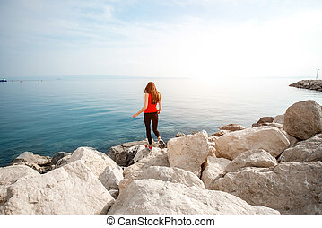 Woman on the rocky beach - Alone sport woman in red jumping...
