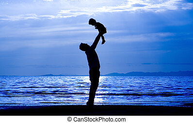 Father and Son - Father throwing his kid up in the air on...