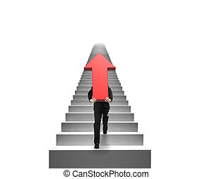 Businessman carrying red arrow sign on stairs with white...