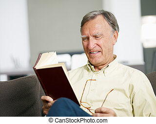 senior man reading book at home Copy space