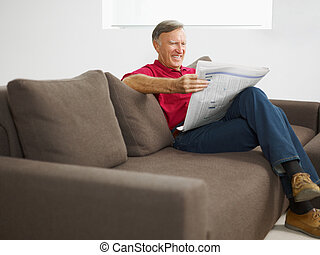 senior man reading newspaper at home and smiling