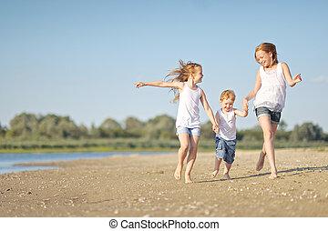 three children playing on beach in summer