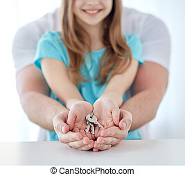 close up of man and girl hands with house keys - people,...