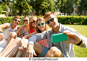 smiling friends with smartphone making selfie - friendship,...