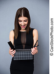 Happy woman in vogue dress opening gift over gray background