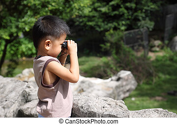 Boy using binoculars looking for something