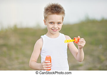 boy and soap bubbles in summer nature