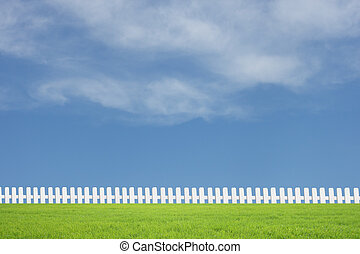 White fences on green grass with blue sky