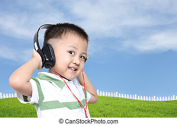 Happy Kid listening to music on headphones with blue sky