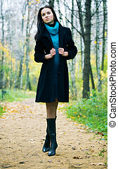Slim brunette woman walking in a park