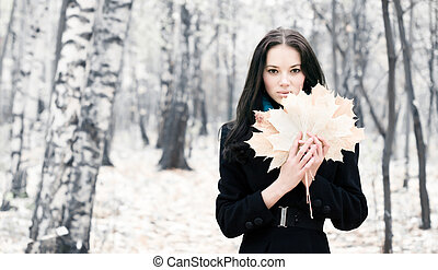 Brunette woman with maple leaves. Bright white autumn forest...