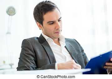 Successful young businessman reading a report - Successful...