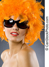 young pretty woman wearing an orange feather wig - picture...
