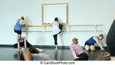 Ballet dancers (ballerinas) stretching and warming up inside...