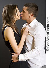 young couple kissing, studio shot - picture of a young...