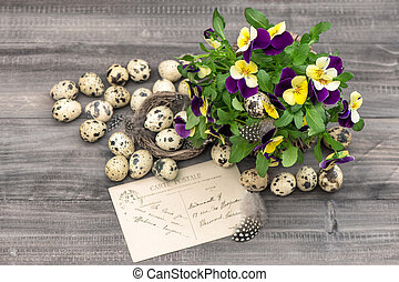 pansy flowers, quail eggs and greeting card. easter...