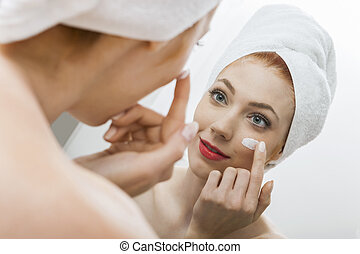 Woman After Shower Applying Cream on her Face