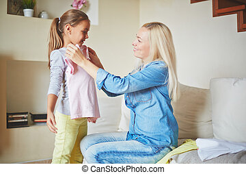 New clothes - Careful mother fitting clothes on her daughter