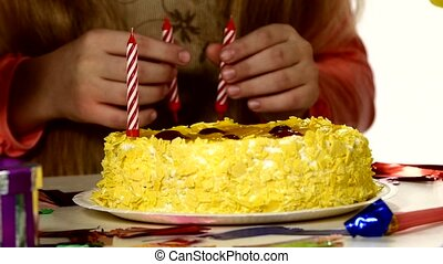 Children put their candles in the birthday cake. Do it one by one. Close up