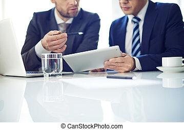 Business meeting - Two businessmen with tablet discussing...