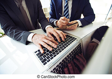 Annual report - Two staff members working with laptop and...