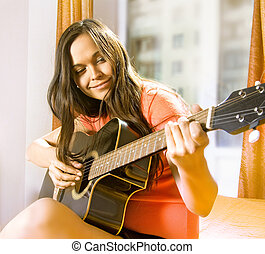 woman with guitar - beautiful young lady in a room with...