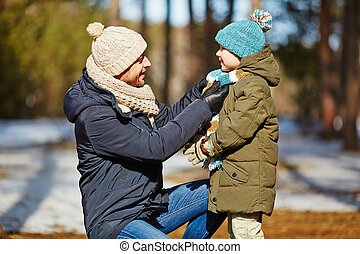 Careful father knotting scarf on son