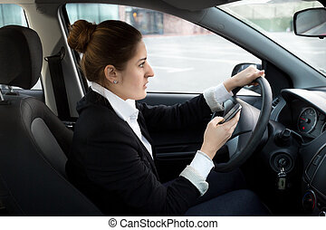 businesswoman typing message while driving a car - Young...