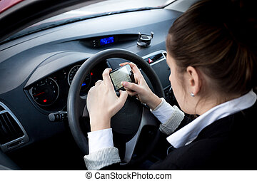 businesswoman typing text on smartphone at car - Young...