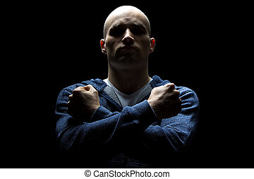 Young hairless man in shadow with arms crossed - Photo of...