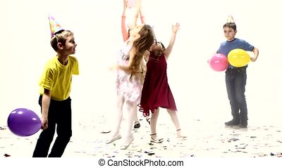 Kids jumping and having fun in a scattered confetti Birthday...
