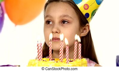 Birthday girl blows out candles on a birthday cake In the...