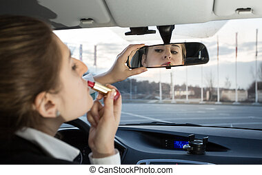 beautiful woman applying lipstick in car - Portrait of...