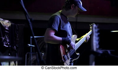 Bass guitar player on a stage - Man playing bass guitar on a...