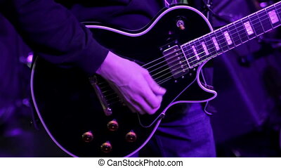 Guitar tuning closeup - Musician tunes the guitar at a...
