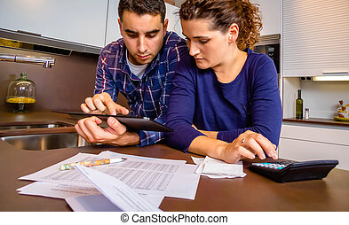 Couple reviewing their accounts with a digital tablet -...