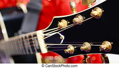Black electric guitar headstock - Musician in red dress...