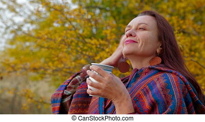 Woman Of Middle Age Drawing A Picture At Plein Air with mug of cocoa in winter