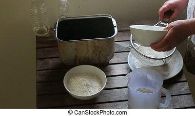 caucasian woman hands sift flour through bolter