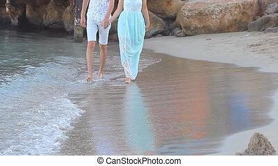 Beach couple walking on romantic travel honeymoon vacation...