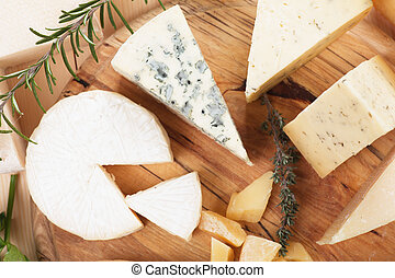 Cheese platter - Assorted cheese on wooden platter, rich and...