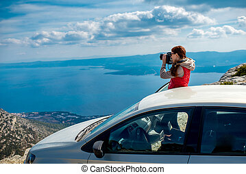 Woman photographer with car on the top of mountain - Young...