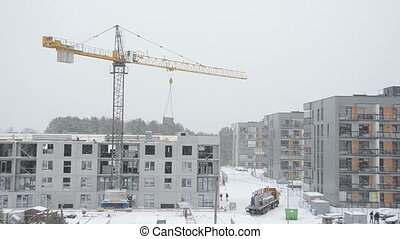 building house winter - Crane lifting concrete block house...