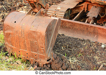 Close up of a big bulldozer scoop on soil