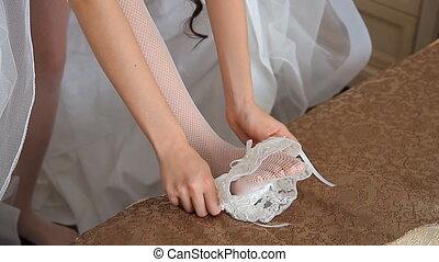 The bride wears a garter - Garter on the leg of a bride,...