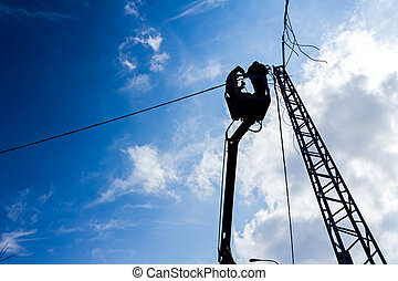 Silhouette of a power line team at work