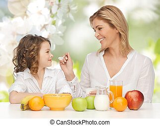 happy mother and daughter eating breakfast - people, healthy...