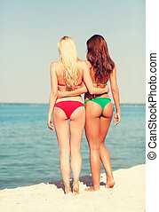 two young women on beach - summer vacation, holidays,...