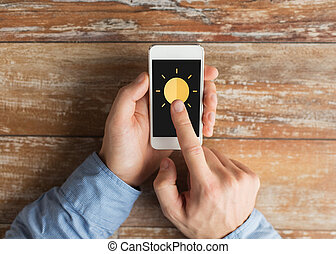 close up of hands with sun icon on smartphone - people,...