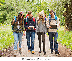 group of friends with backpacks and tablet pc - adventure,...